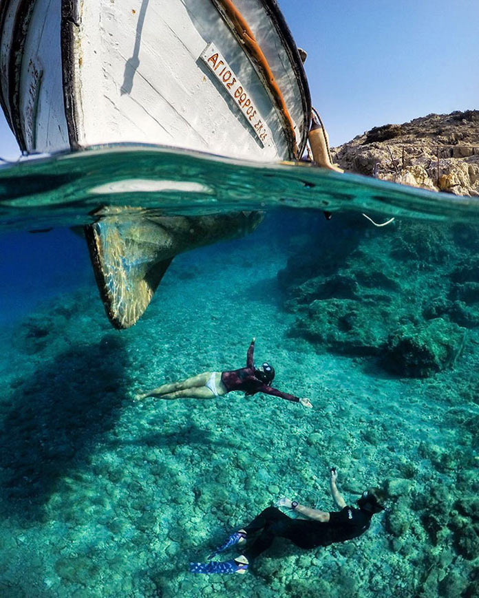 Лодка на прозрачной воде, мужчина и женщина под водой