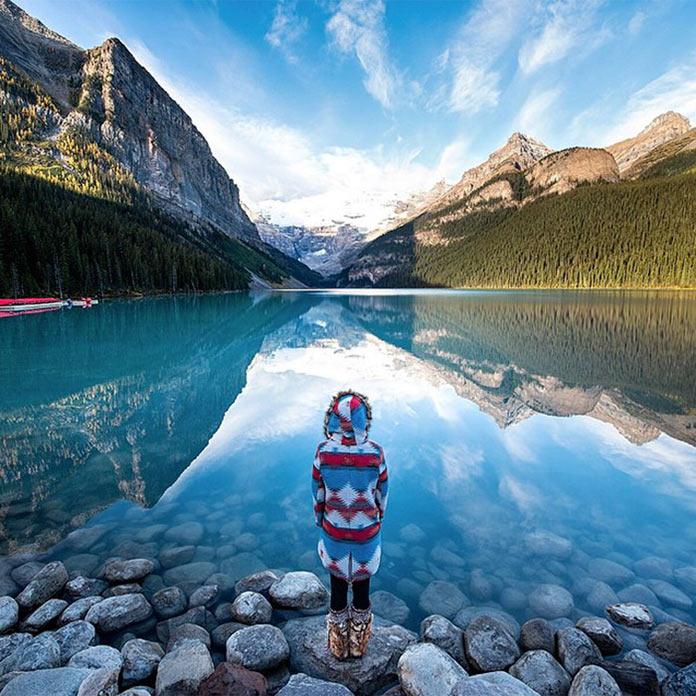 Девушка у чистейшего горного озера с голубой водой