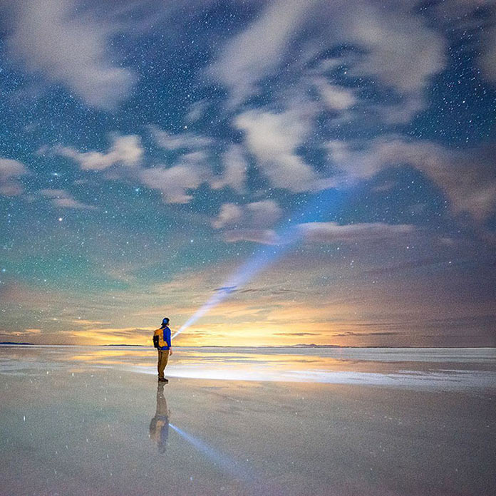 Мужчина под звездным небом на морском побережье