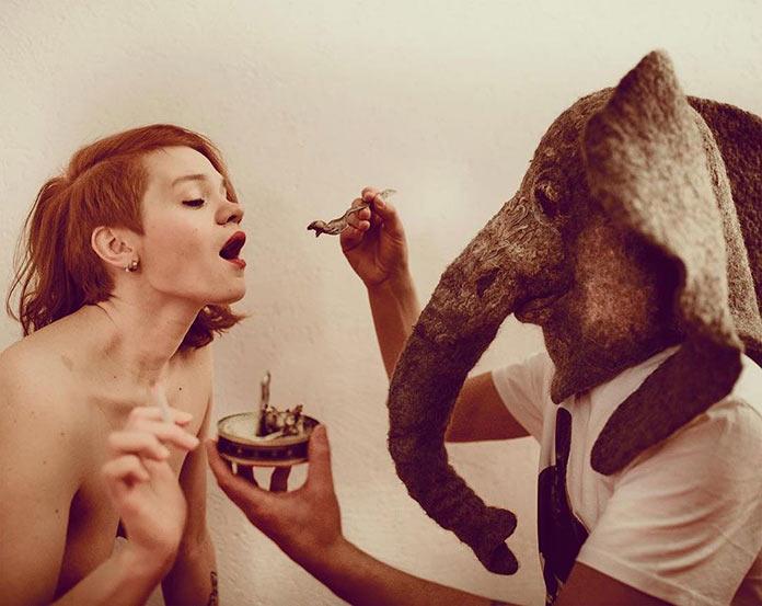 Грустный слон кормит девушку