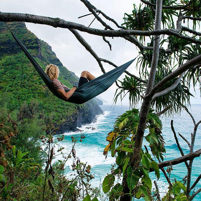 Девушка в гамаке над лесистым морским побережьем