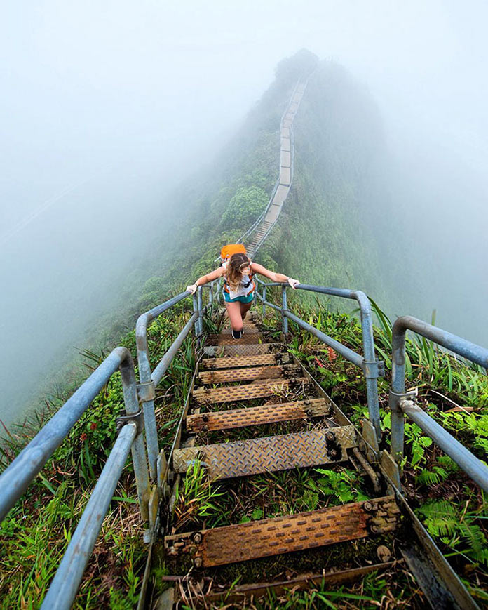 Девушка взбирается по горной лестнице
