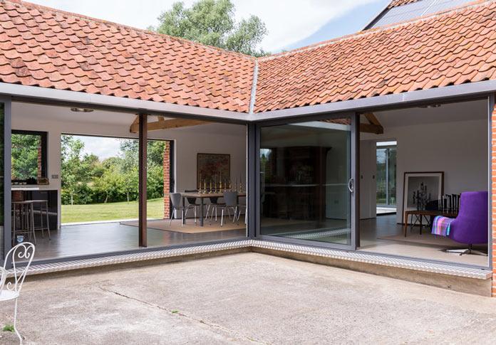 Интерьер деревенского дома в британской провинции. Вид на столовую с панорамными окнами со двора