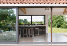 Интерьер деревенского дома в британской провинции. Столовая с панорамными окнами. Вид со двора