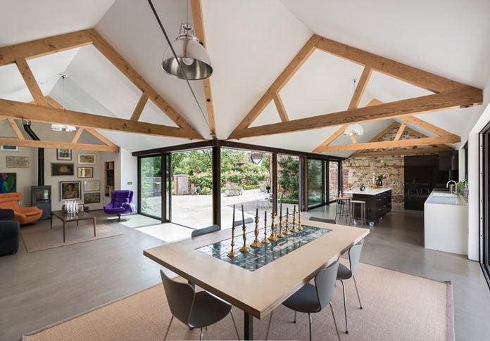 Интерьер деревенского дома в британской провинции. Столовая с панорамными окнами и мини-гостиная с камином