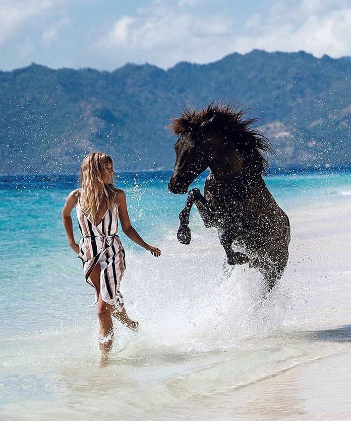 Мэдди Рельф и черный конь бегут по кромке пляжя