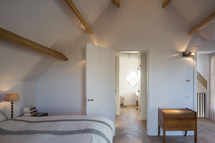 Спальня под скатной крышей и декором из деревянных балок