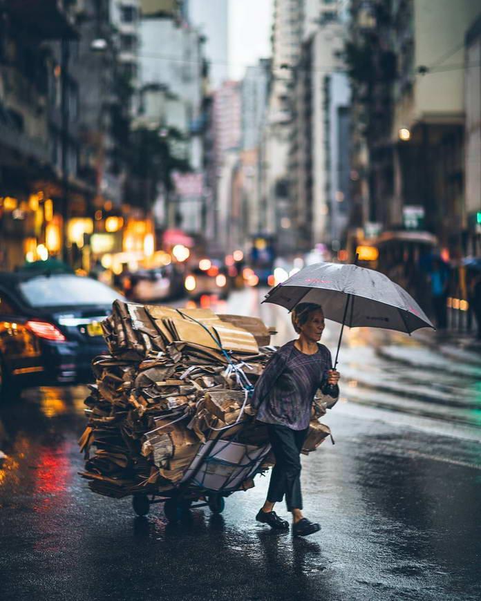 Гонконг, Китай, женщина с зонтом везет тележку с мусором