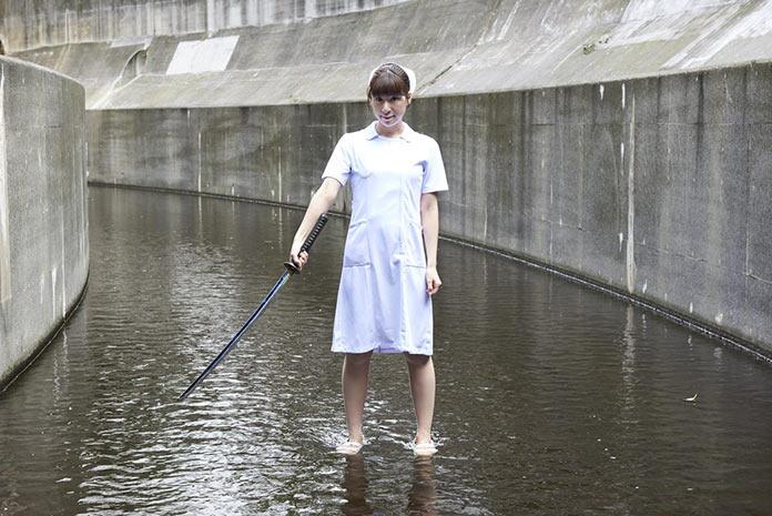 Японская медсестра с самурайским мечом в водоотводном канале