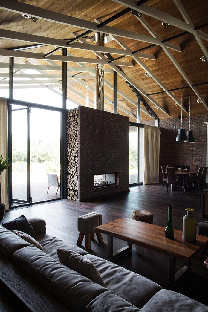 Гостиная и вид на двусторонний камин. Дом в стиле лофт в Ростовской области от архитектурной студии Чадо