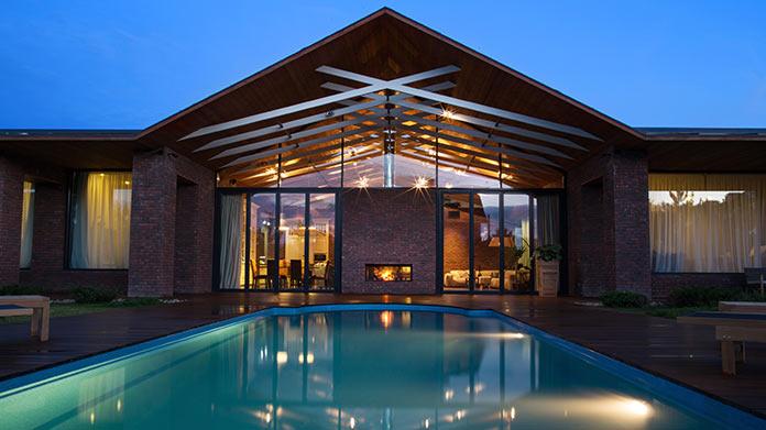 Вид на бассейн и двусторонний камин. Дом в стиле лофт в Ростовской области от архитектурной студии Чадо