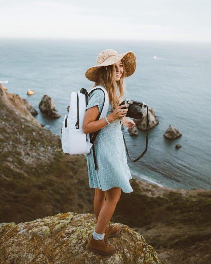 Девушка с фотоаппаратом на скалистом берегу