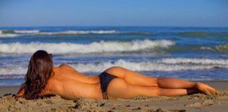 Девушка в бикини лежит на пляже